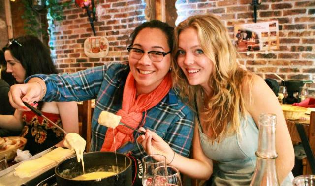 Teenage travelers eat cheese fondue in Paris during summer youth travel program