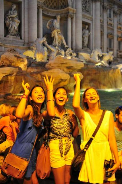 Teen travelers throw coin in Trevi Fountain Rome during summer youth travel program
