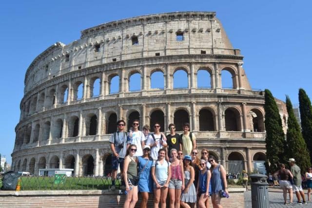 Group of teen travelers at Colosseum in Rome on summer youth travel program.