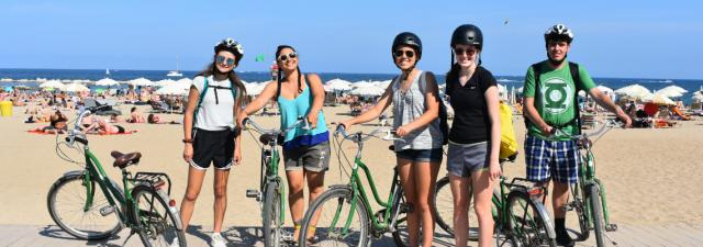 Teens bike on Barcelona beach on Spain summer travel program