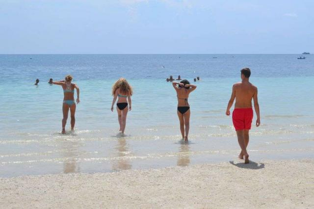 Teenage travelers go swimming in the Pacific ocean during summer youth program in Southeast Asia