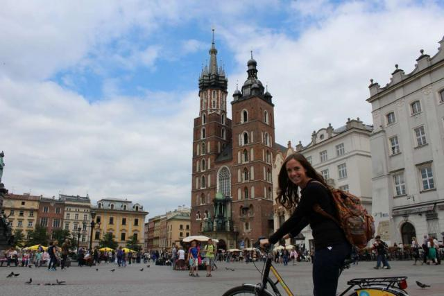 Teen biking through Krakow Main Square on youth summer travel program