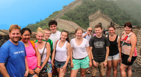 High school travelers pose for a photo on the Great Wall of China on their summer teen tour.