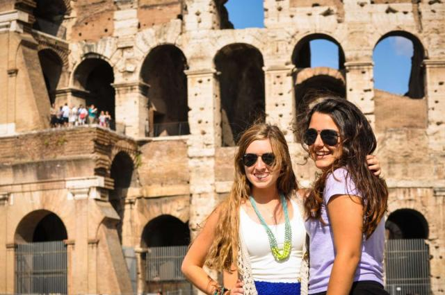 High school students smile in front of the Colosseum on their summer teen tour to Italy.