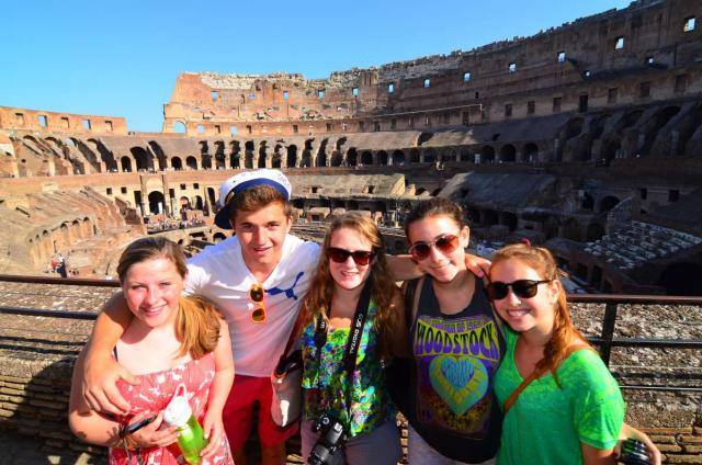 High school students smile in the Colosseum on their summer teen tour to Italy.
