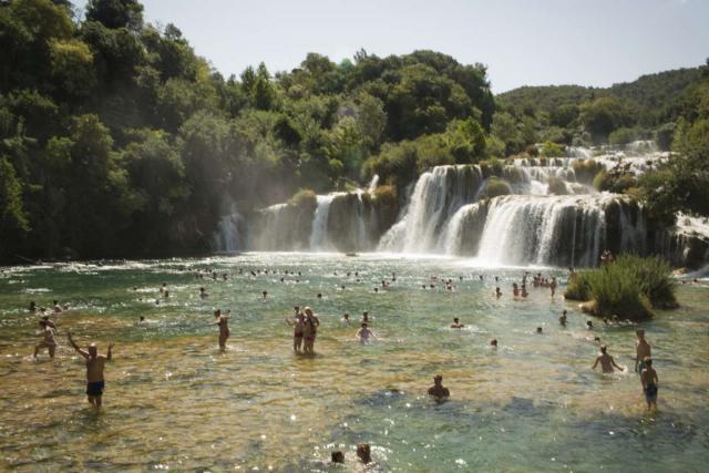 Teen travelers swim at Krka Waterfalls on summer youth adventure program