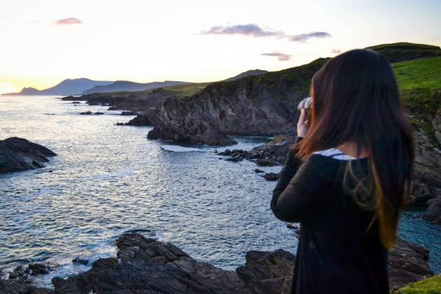 Teenage traveler photographs sunset over Irish cliffs during summer teen travel program