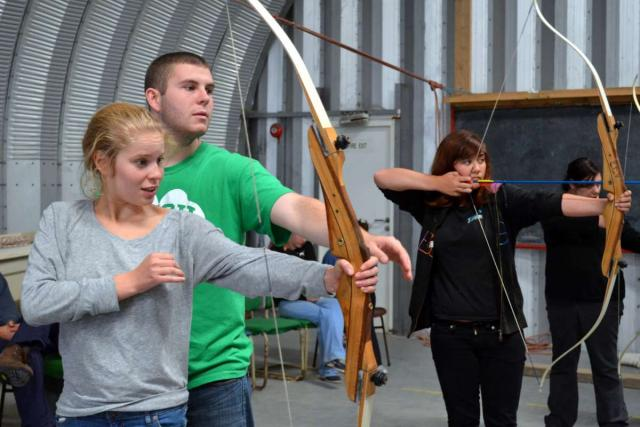 Teen travelers practice archery bow and arrow during summer youth adventure travel program in Ireland