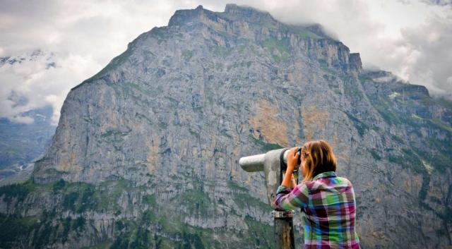 Teen traveler exploring Swiss Alps during summer adventure travel program