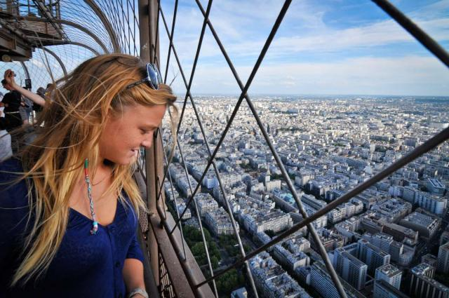 Younger teen traveler looks out at Paris from atop Eiffel Tower during summer student travel program in France