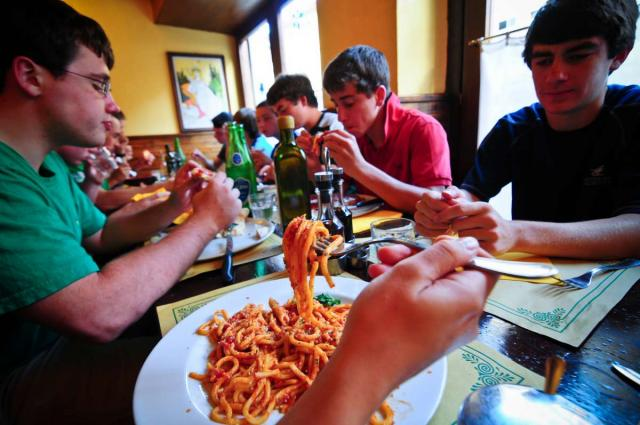 Teenage travelers eating authentic local cuisine in Italy on summer travel program