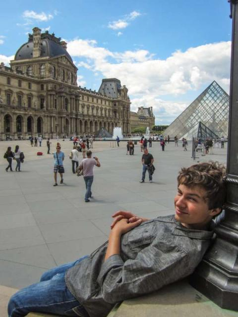 Teen traveler relaxes at Louvre Museum on summer student travel program in France