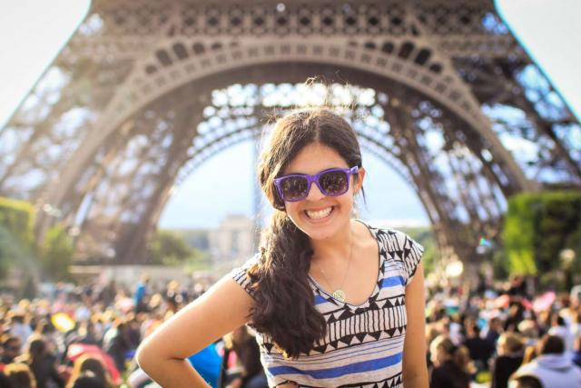 Teen traveler poses in front of Eiffel Tower on summer travel program to France