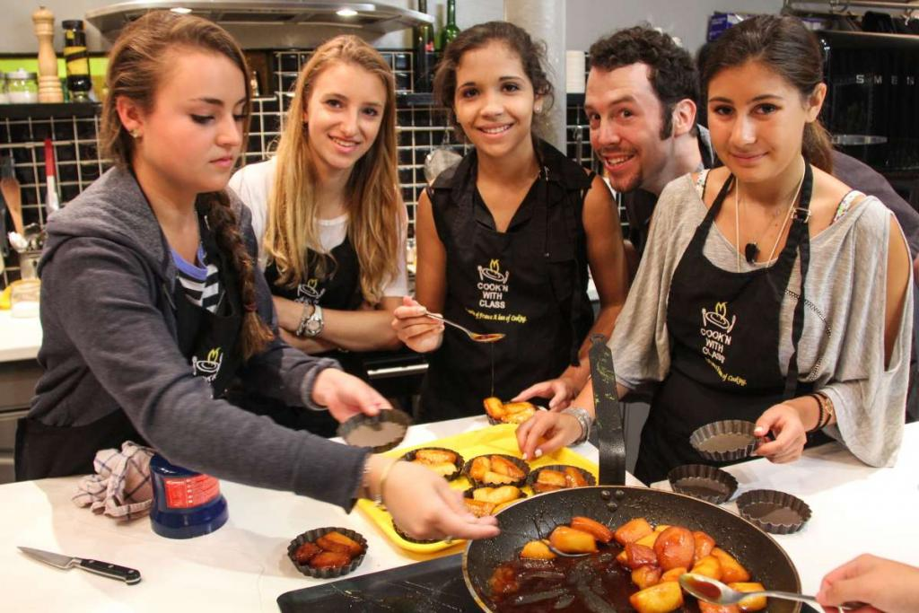 Teenage travelers at cooking lesson in Paris during French summer language immersion program
