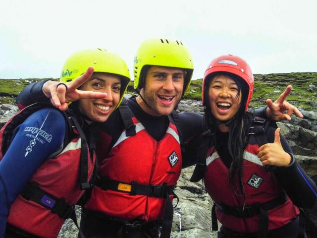 Teen travelers coasteering in Ireland during summer youth adventure travel program