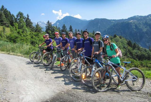 Teens bike in Alps mountains on summer youth travel program