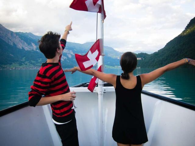 Teenage travelers cruising on Swiss lake Interlaken on summer travel program
