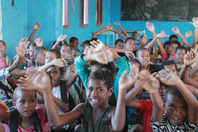 Fijian children smile and wave during summer youth program in Fiji