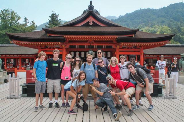 Teenage travelers pose with Japanese temple during summer youth travel program in Japan