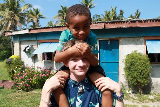 Teen traveler with local Fijian child during summer youth program in Fiji
