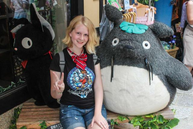 Teenage traveler poses with Japanese cartoon character during summer youth travel program in Japan