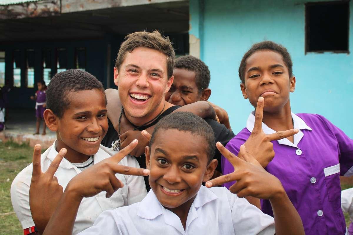 Teen traveler having fun with local Fijian children during summer youth program in Fiji