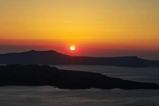 Teenage travelers watch sunset over Greek island during summer youth travel program in Greece