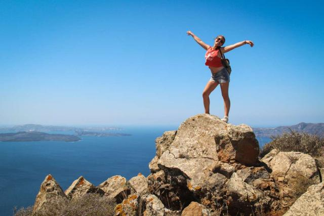 Teenage traveler climbs mountain for breathtaking scenic views during summer youth travel program in Greece
