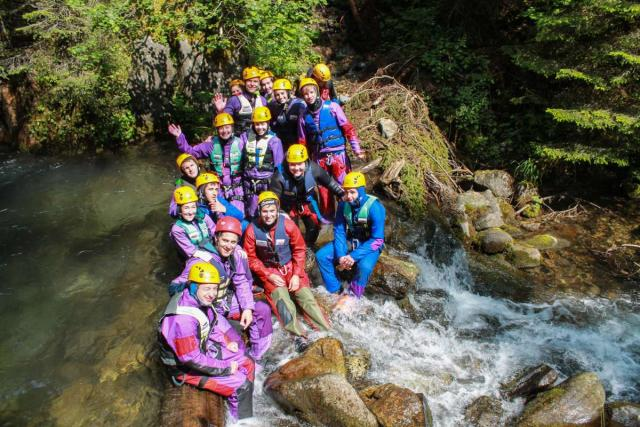 Teen travelers canyoning in Switzerland during summer travel adventure program