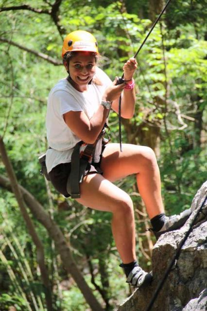 Teenage traveler on rock climbing adventure during summer youth travel program in Thailand