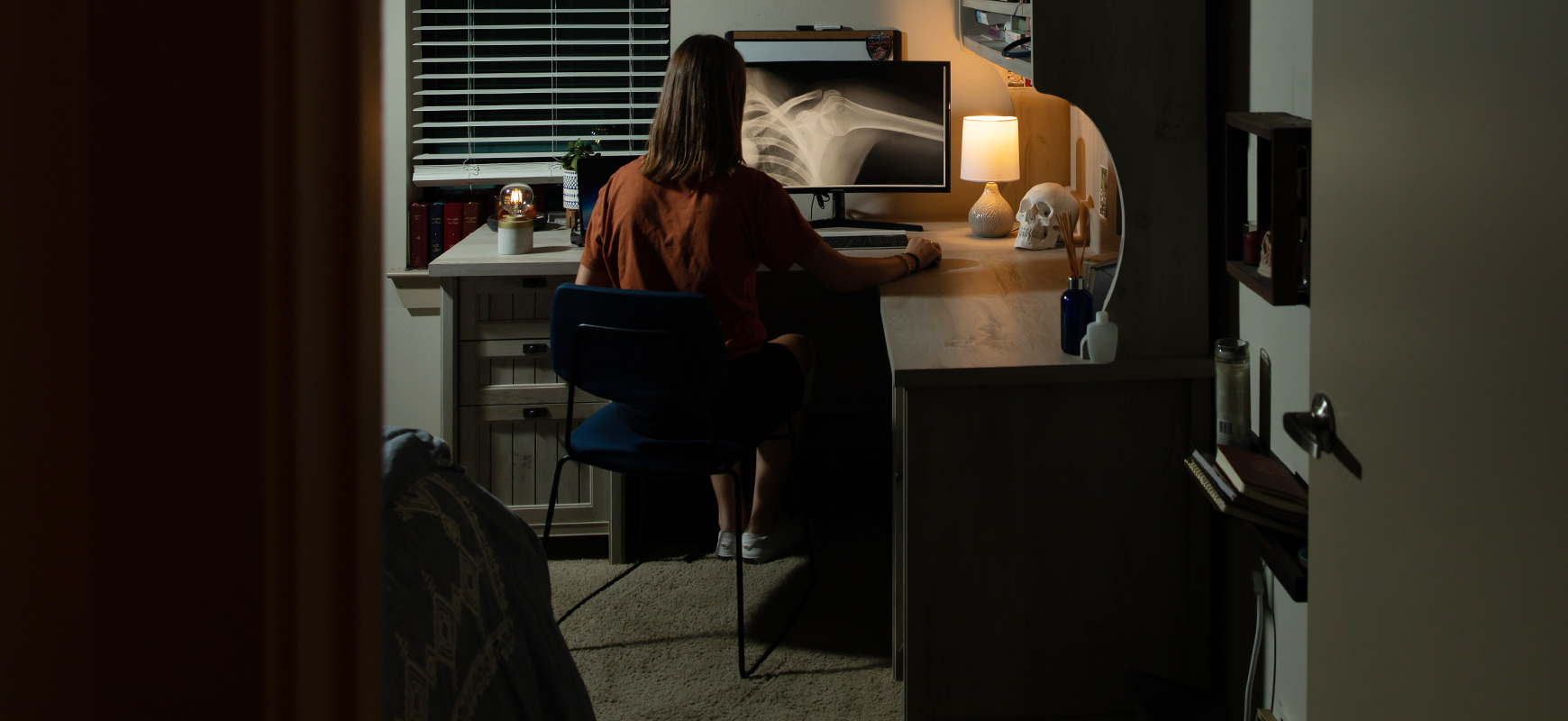 A Dell Med student sits at a desk in her home.