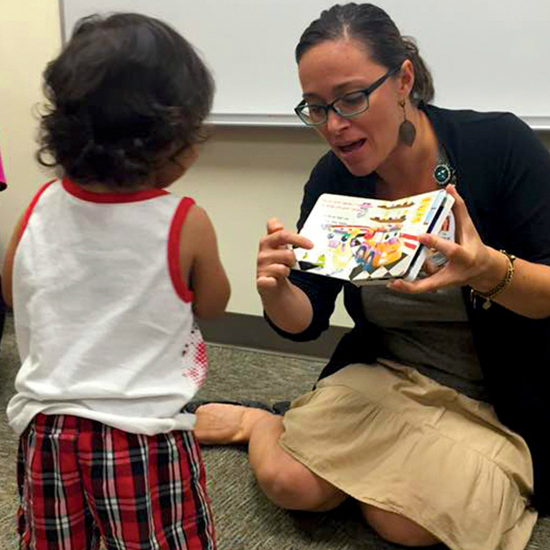 A woman reading a book to a child.