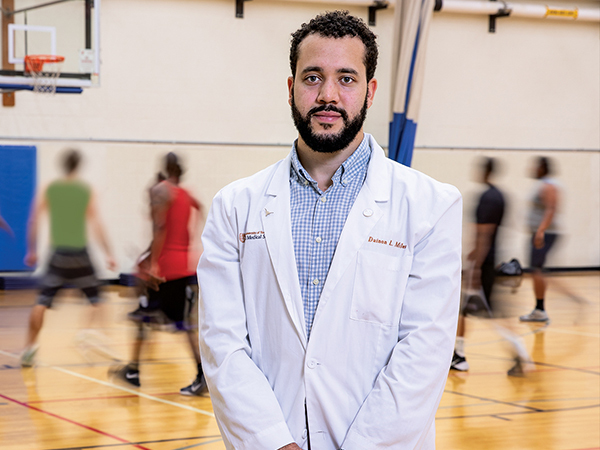 Medical student stands on basketball court as people play in the background