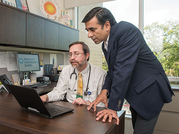 A researcher and physician view data on a laptop