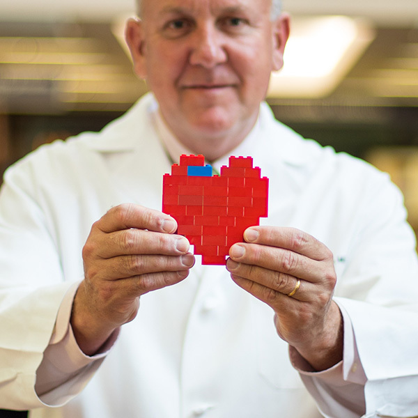 Charles Fraser holding a heart made of Legos.