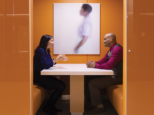 Two individuals have a conversation in orange subway booths