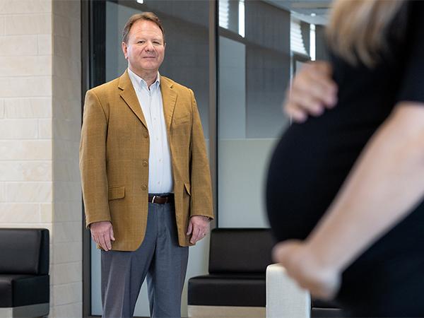 A man standing near a pregnant woman.