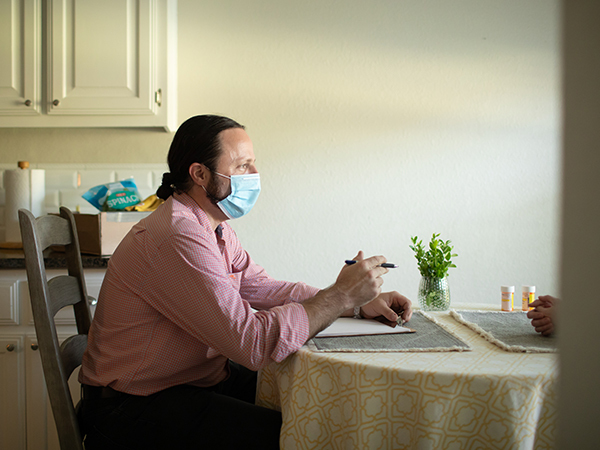 A man wearing a surgical mask sits at a table talking with someone.