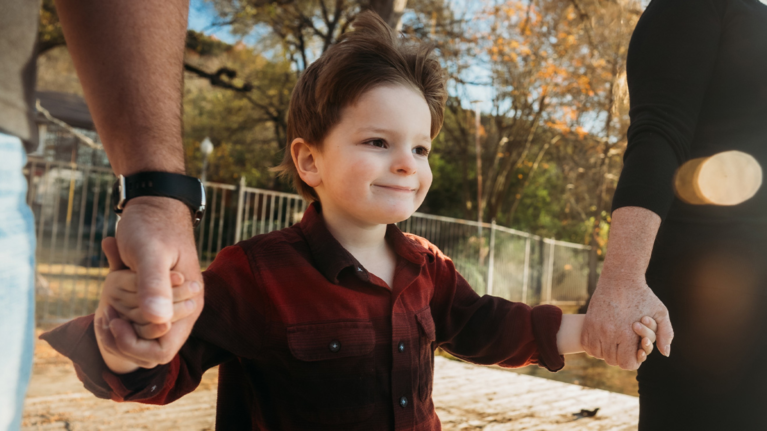 4-year-old boy (Levi Reeves) holding his parents hands during walk.
