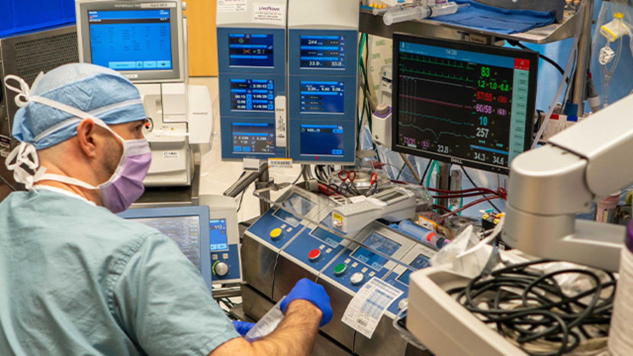 Perfusionist sitting at cardiopulmonary bypass machine.