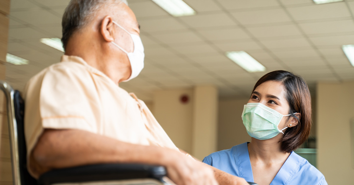 Medical provider speaking with patient in wheelchair