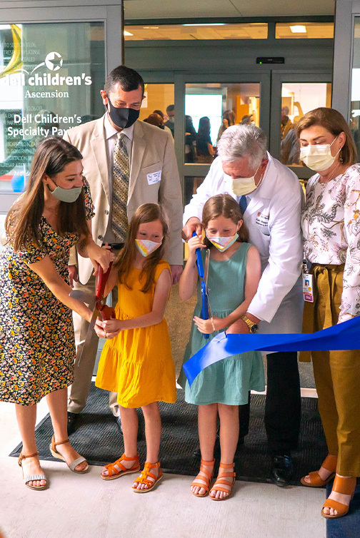 Amber Cessac and her twin daughters join Dr. Kenneth Moise for a ceremonial ribbon cutting