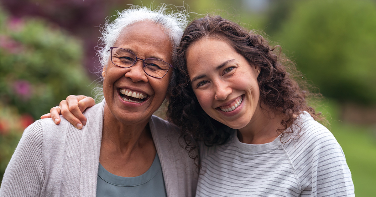 Woman smiling and hugging her elder mother
