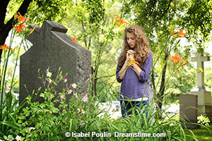 Young girl praying in a Cemetary