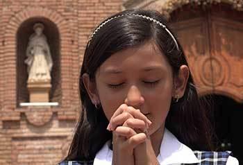 Girl praying outside a church
