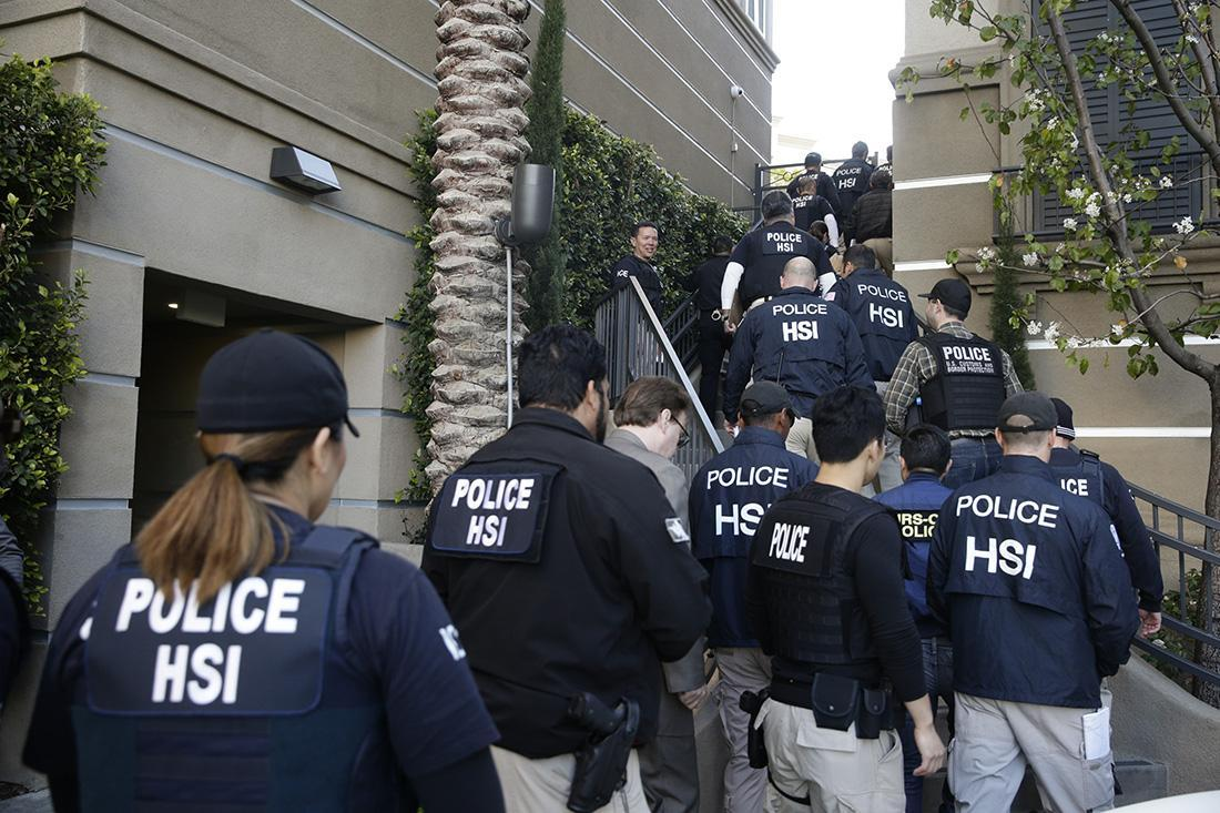 Federal agents at an apartment complex in Irvine, Calif., where, according to authorities, a birth tourism business operated in 2013