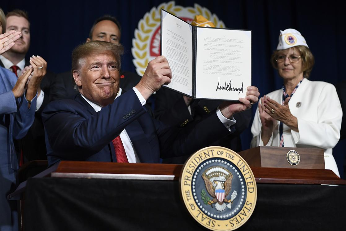 President Donald Trump holds the order discharging student loan debt for disabled veterans at a signing ceremony in Louisville, Ky., on Aug. 21.