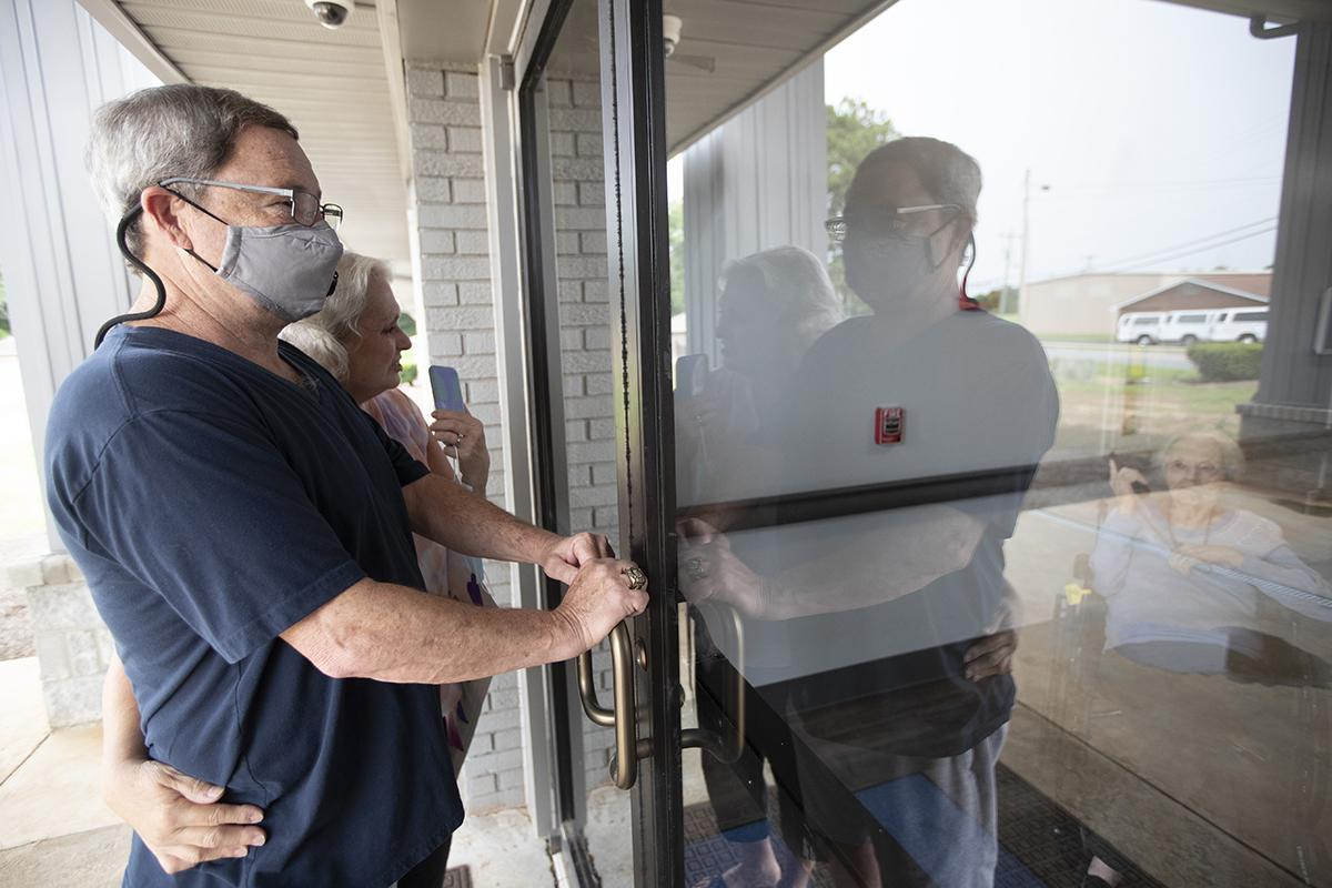 Southern Pines nursing home resident Shirley Campbell (left) visits with family through a glass door in Warner Robins, Ga.