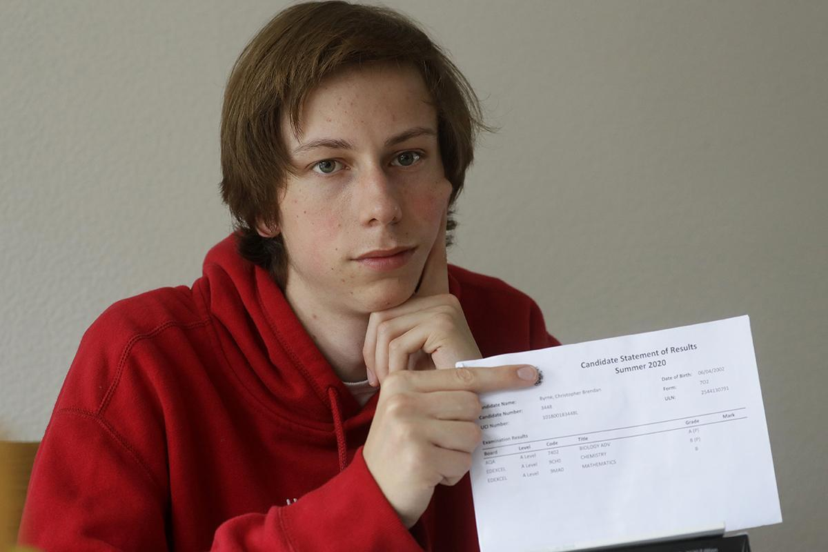 A-level student Chris Byrne holds his teacher-predicted results in London.