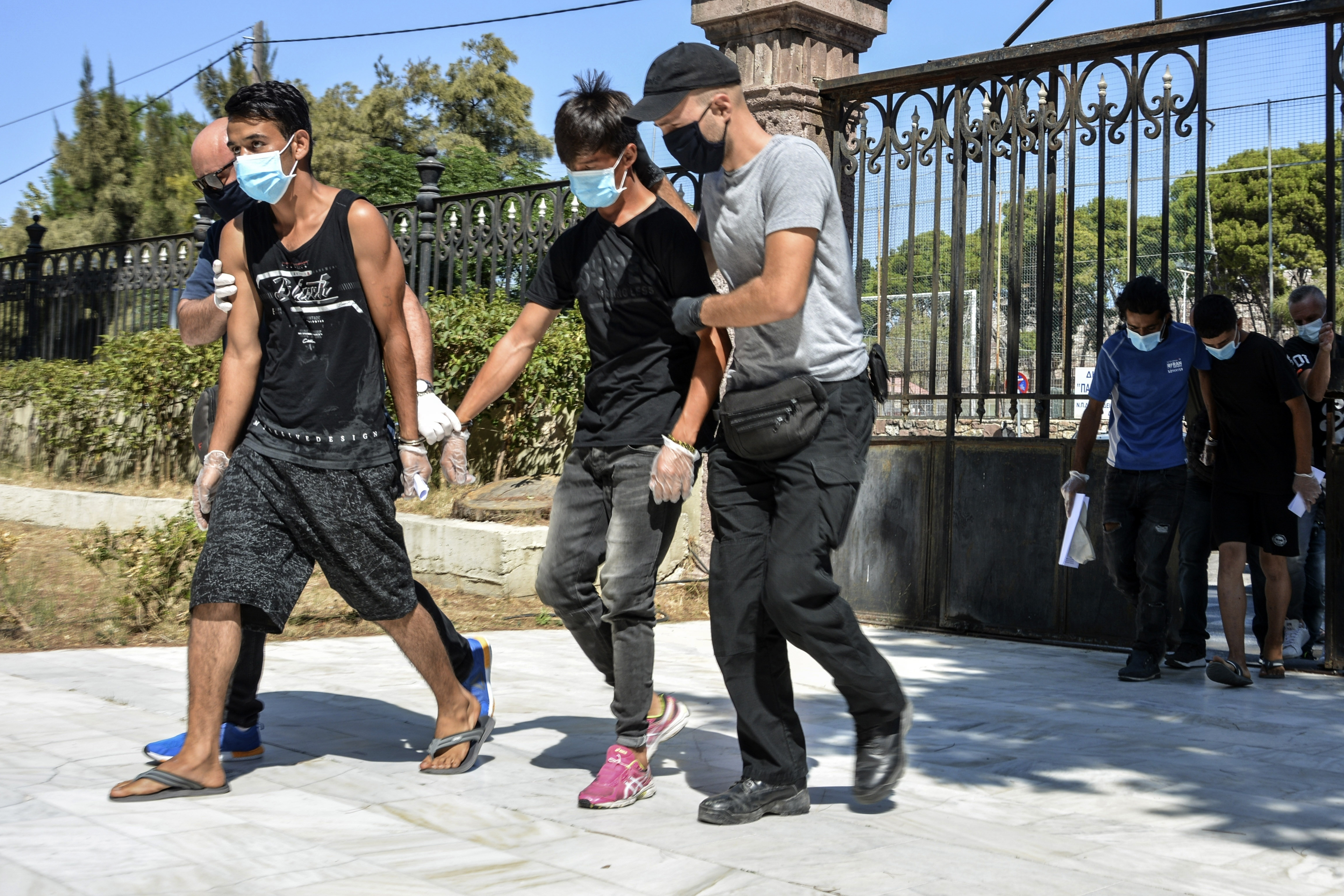 Young Afghan suspects arrive at a court in Mytilene, Greece.